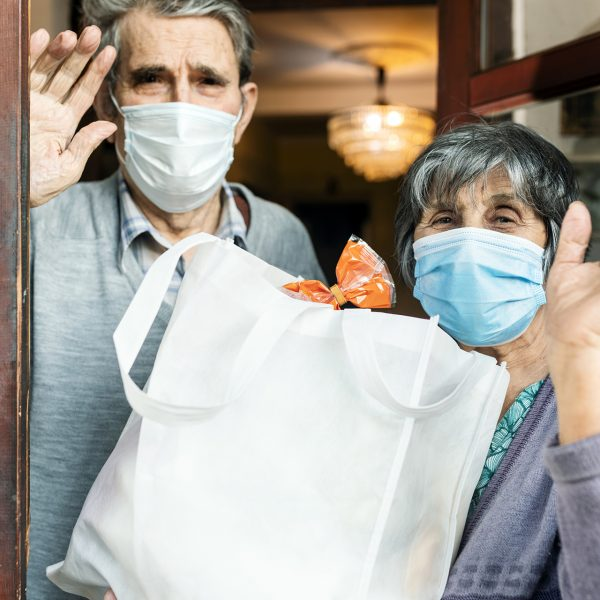 Senior couple, during isolation,COVID 19.They standing at the front door and holding a bag with supplies.  Looking at camera.They wave by hands.